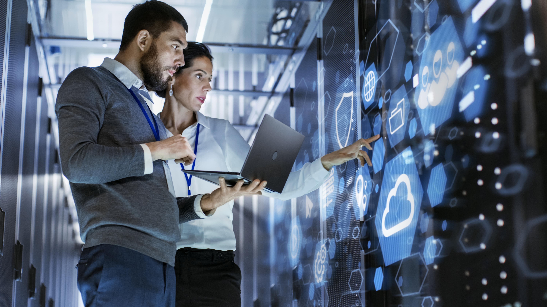 Mann und Frau bedienen einen Laptop, vor ihnen entsteht eine digitale Lernwelt